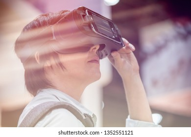 Young woman using virtual reality goggles. Concept of modern technologies.