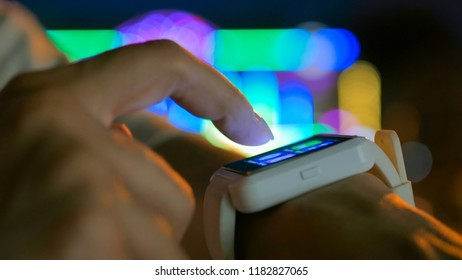 Young woman using wearable smartwatch computer device in the city - scrolling and touching. Evening time, twilight, colourful bokeh background. Relax, entertainment and technology concept