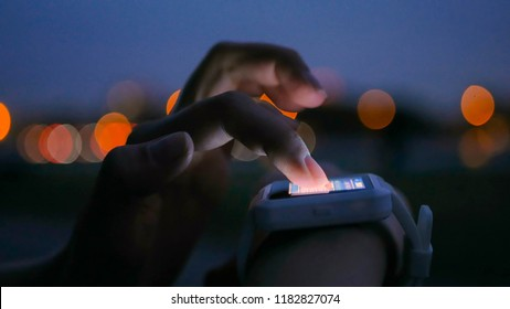 Young woman using wearable smartwatch computer device in the city. Evening time, twilight. Relax, entertainment and technology concept