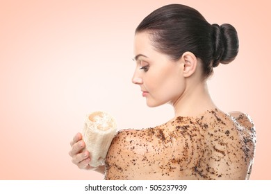 Young woman using wisp and scrub on color background. Skin care concept.