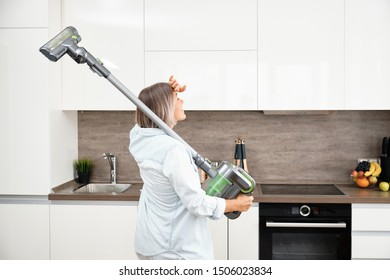 A Young Woman Vacuuming the Floor. Cleaning in the House. Vacuum Cleaner in kitchen.