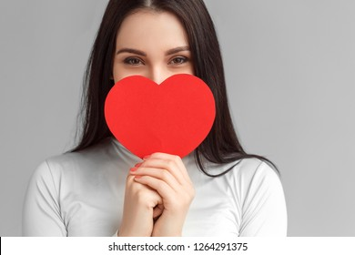 Young woman valentine's day concept studio standing isolated on gray wall covering mouth with heart shaped card looking camera smiling cheerful close-up