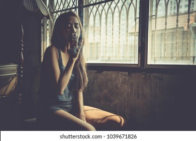 Young woman vaping, blowing cloud of smoke. Nicotine addiction toxic dangerous for healthy. Girl Smoking Cigarette in dark dirty room with copy space.
