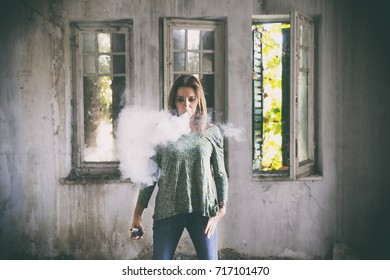 Young woman vaping on an abandoned house. Studio shot. Black background