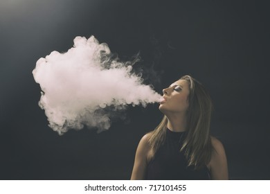 Young woman vaping. Studio shot. Black background