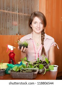 Young woman with various seedlings at home