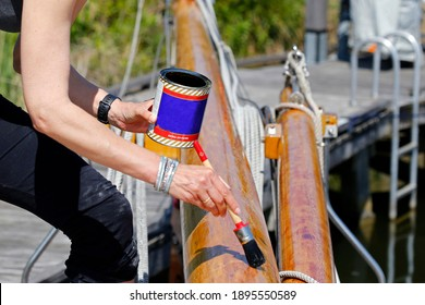 A young woman varnishing the wooden mast of a classic sailing yacht