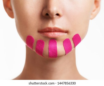 Young woman with vertical kinesio tapes on chin for facelift, front view. Anti-aging and beauty procedure.