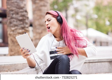 Young woman very excited listening to music on the tablet in the street