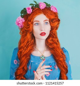 Young woman with very long hair in flower dress with expensive jewellery on blue background. Renaissance fairy princess with pink roses in hair. Jewellery in the style of the middle ages