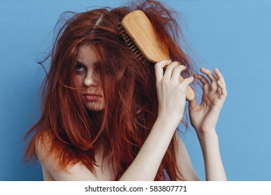 Young woman with a very tangled hair trying to comb your hair