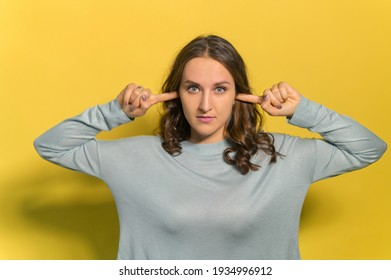 Young woman vexed with noise covering ears with fingers, a girl does not want to listen loud music, no desire to listen to an opponent in an argument, studio shot isolated on yellow