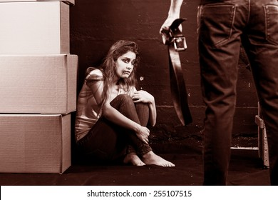 Young woman is a victim of domestic violence and abuse siting on the floor is scared of man with belt on brown background