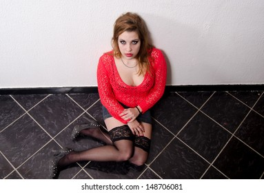 Young woman victim of human trafficking sitting on the floor.