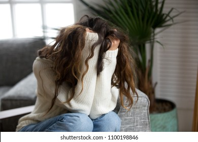 Young woman victim suffering from abuse, harassment, depression or heartbreak, sad desperate teenager having problems holding head in hands, heartbroken upset girl crying having dangerous addiction