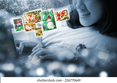 Young woman viewing christmas photos by using laptop