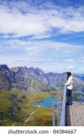 Young woman in a viewpoint of Swiss Alps