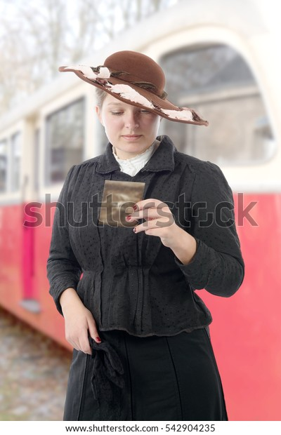 young woman in  vintage costume 1900s, old train background
