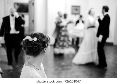 Young woman in vintage dress sitting at ball and looking at couples dancing on dance floor. Retro dances historical reconstruction.