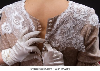 A young woman in vintage lingerie and white gloves unzips her girlfriend's dress, a lot of buttons. Added a small grain, imitation of film photography.