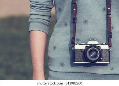 young woman with vintage, retro analog single-lens reflex camera