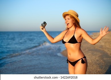 Young woman with vintage retro film camera enjoying tropical beach on summer vacation. Female body positive photographer in bikini swimsuit taking photos having fun at sea. Real unretouched shape girl