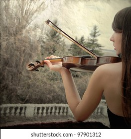 Young woman with a violin in the park