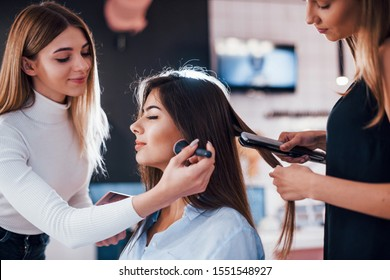 Young woman visit the beauty salon and get service from two female workers.