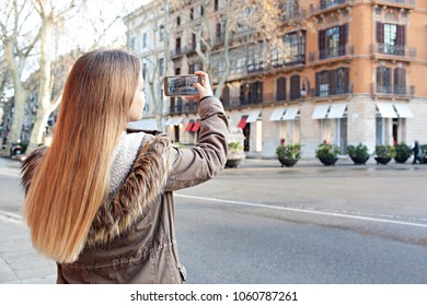 Young woman visiting destination city on holiday using smart phone to take pictures outdoors. Tourist female holding device sightseeing photo on screen. Technology travel recreation leisure lifestyle.
