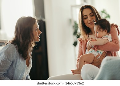 Young woman visiting a female friend and her baby daughter at home.