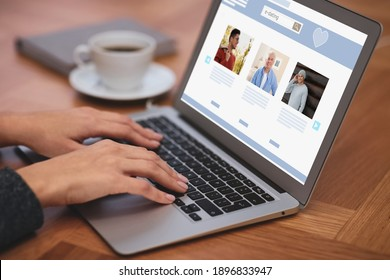 Young woman visiting online dating site via laptop at table, closeup