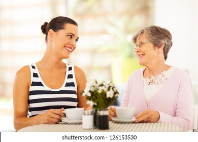 young woman visiting senior mother and having coffee together