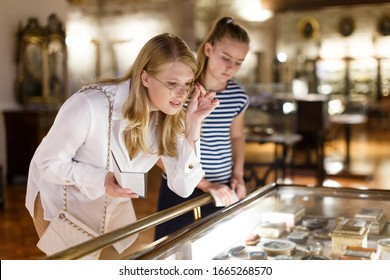 Junge Frau Besucher mit Tochter, die Kunstobjekte unter Glas mit Führer im Museum sucht