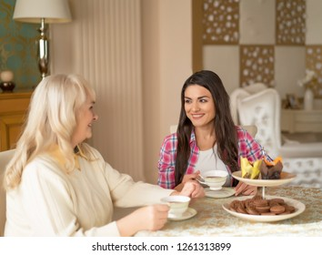 Young Woman Visits Her Senior Mother And Drinks Coffee Together With Her. Family Time Together At The Table Drinking Tea