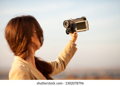young woman vlogger recording her video outdoors