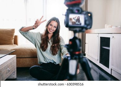 Young woman vlogger showing victory or peace sign while recording her daily video blog. Vlogger using a camera mounted on a tripod to record her video.