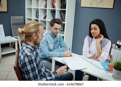 Young woman voicing her ideas about architectural project to co-workers