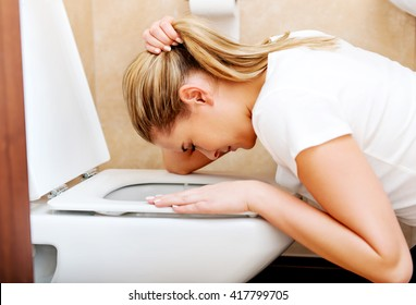 Young woman voimiting in the bathroom