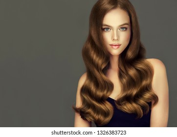 Young woman with voluminous brown-colored hair.Beautiful model girl  with long, dense, curly hairstyle .