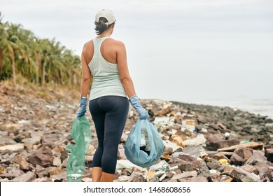 Young woman volunteer in gloves holds plastic garbage on the background of sea coast.