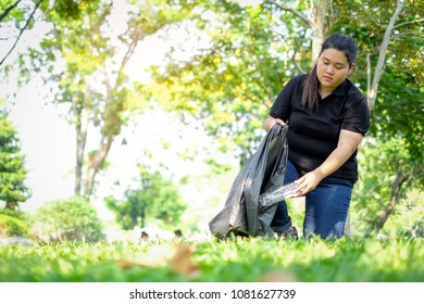 young woman volunteers picking up trash in park. Concept of environmental protection