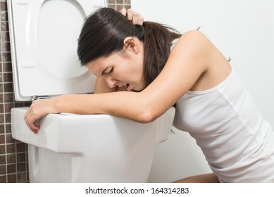 Young woman vomiting into the toilet bowl in the early stages of pregnancy or after a night of partying and drinking