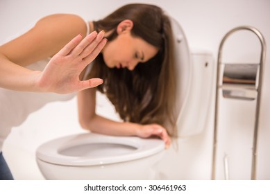 Young woman vomiting into the toilet bowl in the early stages of pregnancy or after a night of partying and drinking.