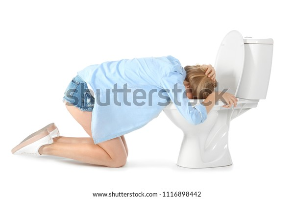 Young woman vomiting in toilet bowl on white background