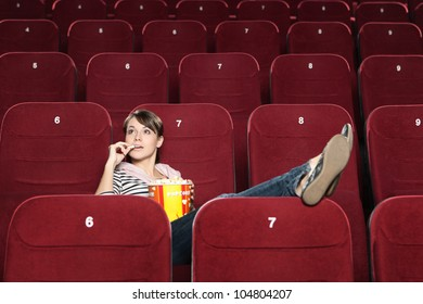 Young woman wait for a beginning of the movie