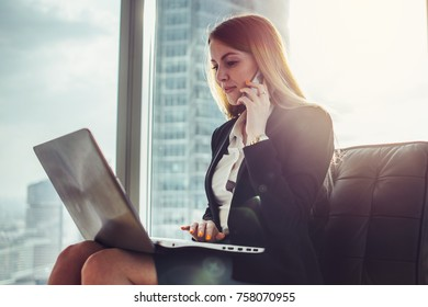 Young woman waiting in a hall sitting in modern office working on laptop talking on the phone