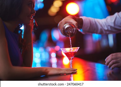 Young woman waiting for her martini in the bar