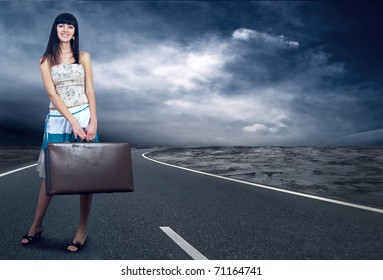 Young woman waiting on the road with her vintage baggage