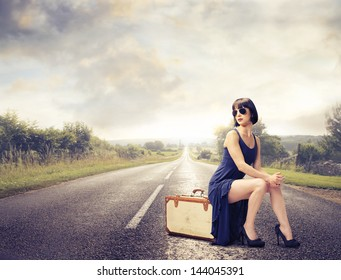 young woman waiting sitting on the suitcase on the road