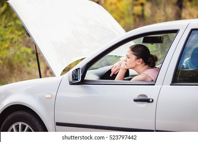 Young woman waits for assistance in her car, which broken down on the road side.